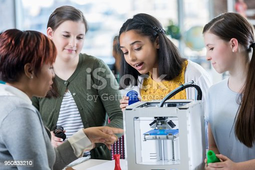 Female high school students and their teacher use 3D printer in class. The teacher is teaching the girls how to use the printer to create items.