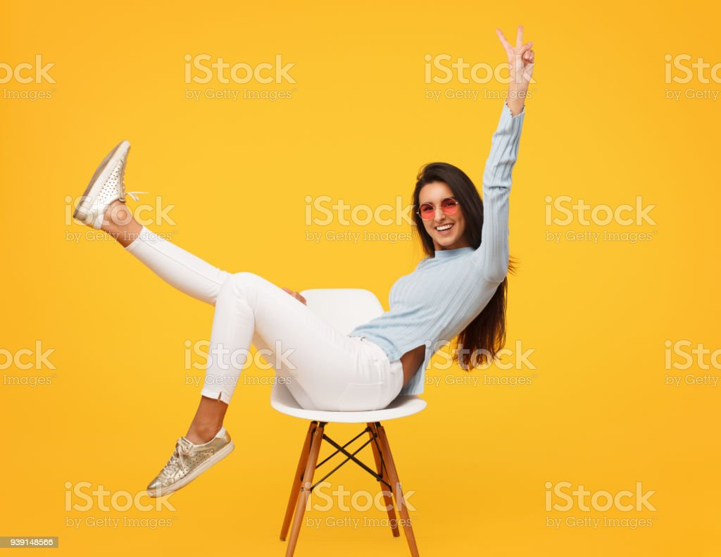Excited hipster girl posing on chair stock photo