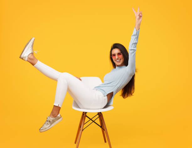 excited hipster girl posing on chair - sitting stock pictures, royalty-free photos & images