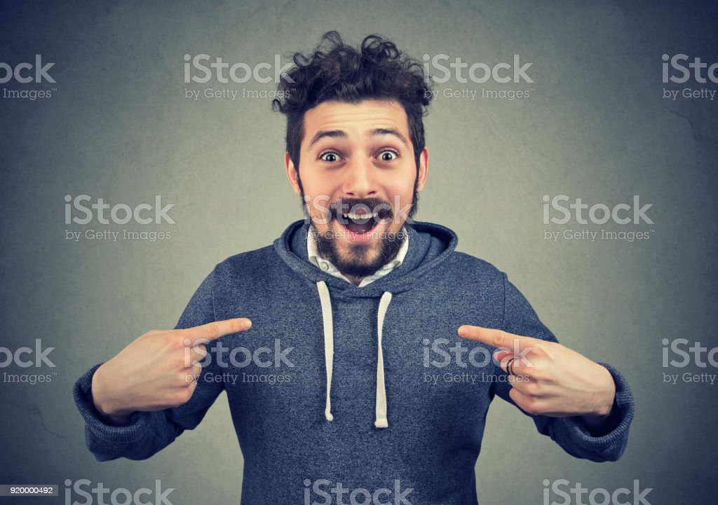 Excited hipster pointing at himself in astonishment stock photo