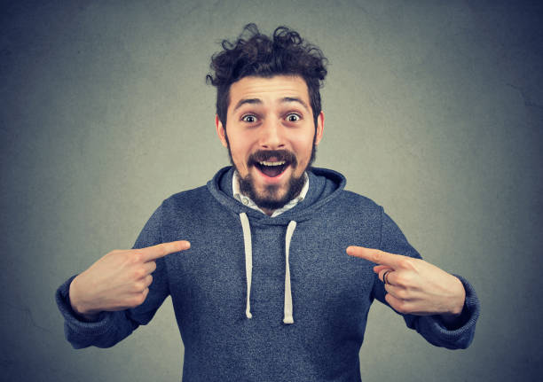 excited hipster pointing at himself in astonishment - one man only stock pictures, royalty-free photos & images