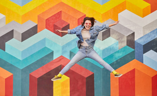 Excited hipster woman jumping high on colorful background stock photo