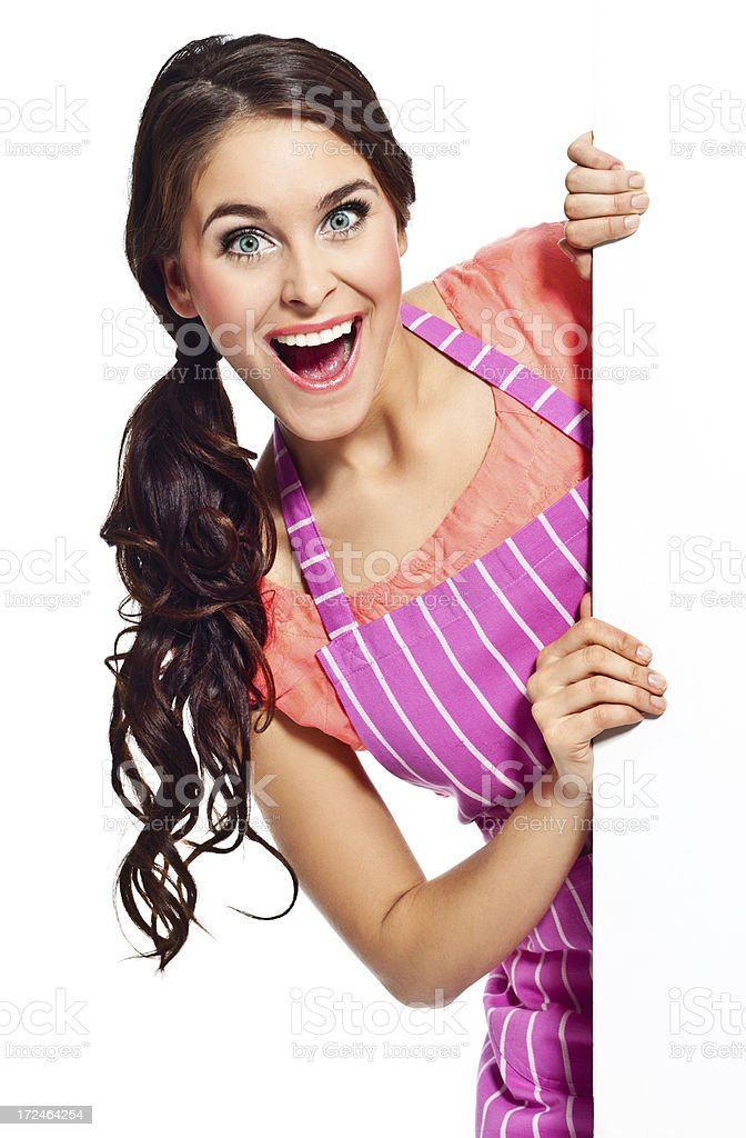 Excited housewife with whiteboard Portrait of happy young woman wearing an apron holding a whiteboard and laughing at the camera. 20-24 Years Stock Photo