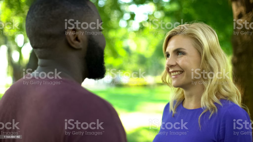 Excited interracial couple looking at each other, emotions of...