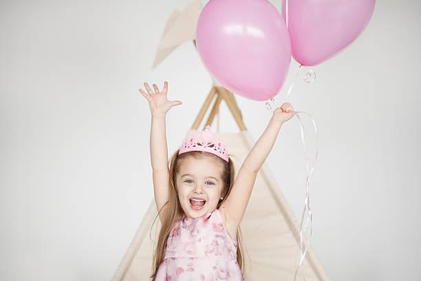 excited kid celebrating her birthday - festliche babymode junge stock-fotos und bilder