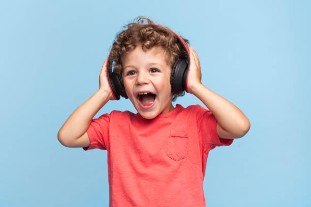 Excited kid posing in headphones stock photo