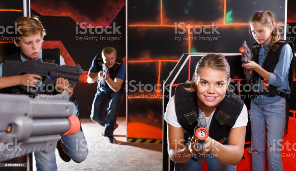 Excited Kids And Theirs Parents Playing Laser Tag Game In Dark Room