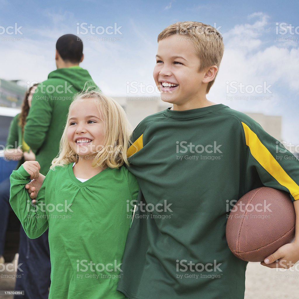 Excited kids at football stadium, tailgating with family royalty-free stock photo