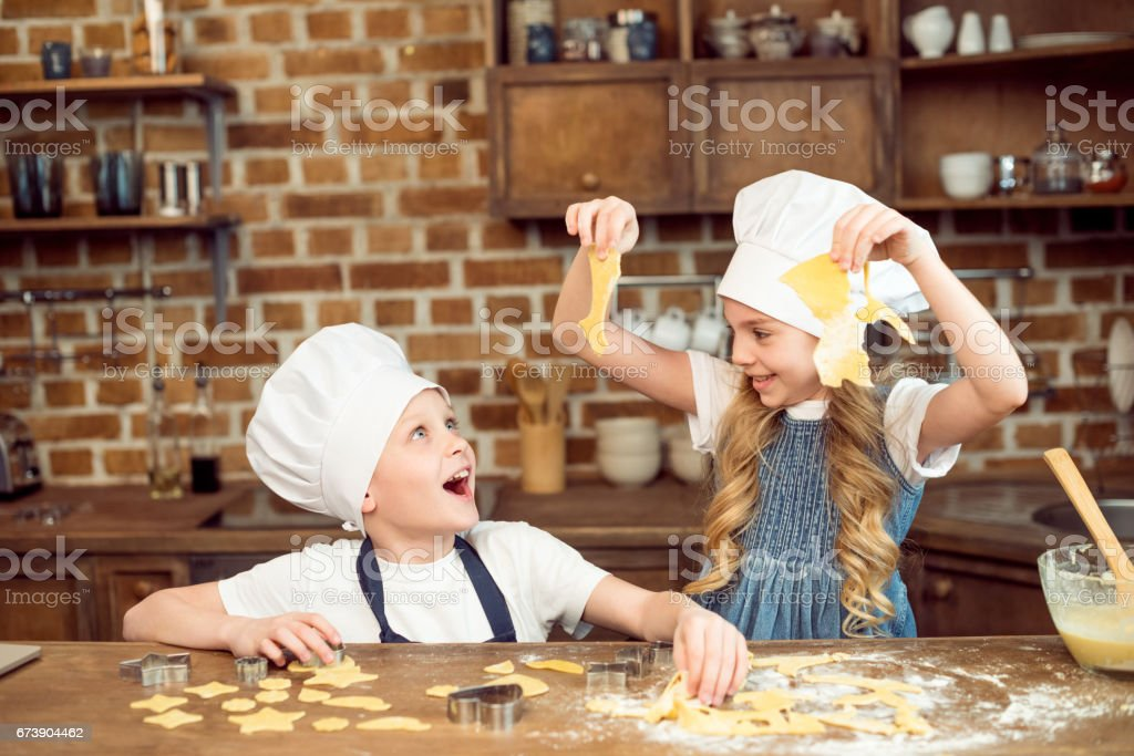 excited kids playing with dough for shaped cookies in kitchen foto de stock royalty-free