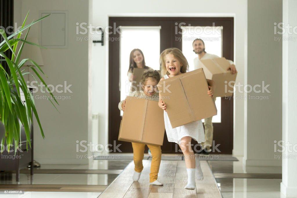 Opgewonden kinderen lopen bedrijf vakken, familie bewegen in nieuwe woning foto
