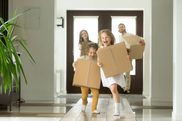 Excited kids running holding boxes, family moving in new house stock photo