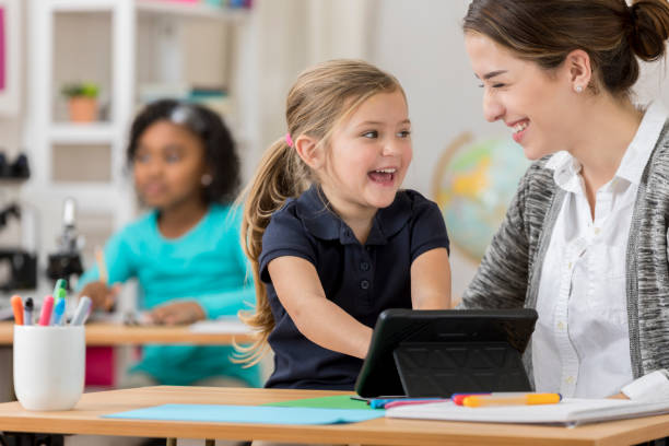 Excited kindergarten student uses digital tablet at school stock photo