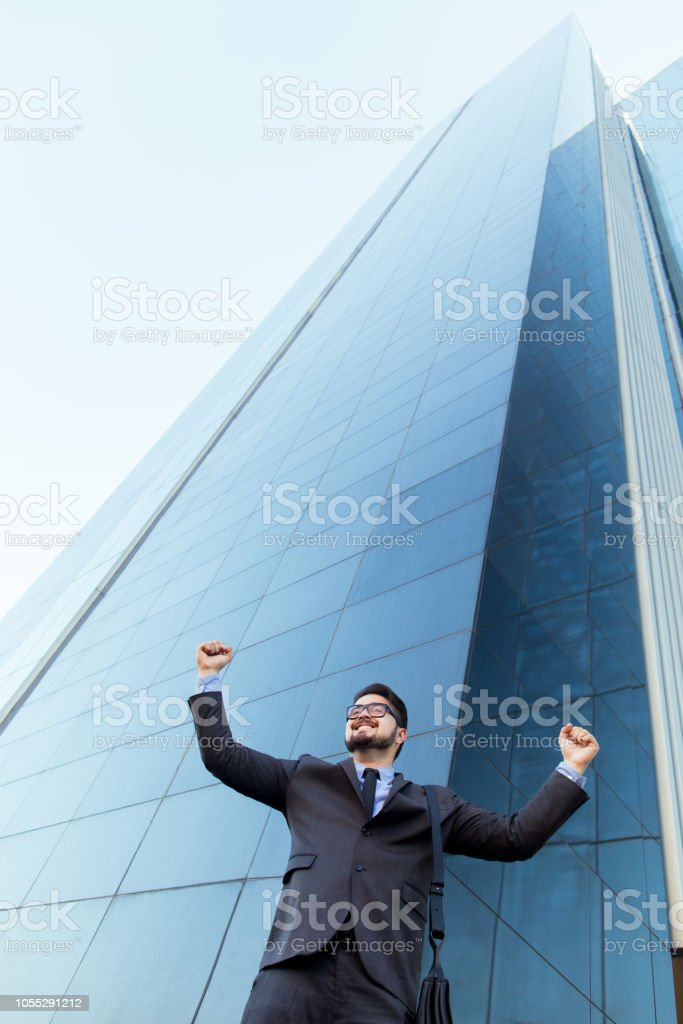 Excited latin business man raising hands stock photo