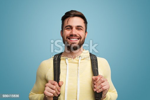 istock Excited laughing male student on blue 936415836