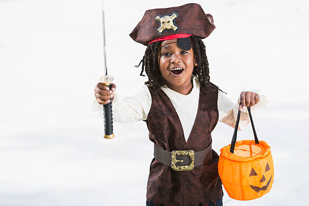 Excited little boy in halloween costume African American boy (6 years) wearing pirate halloween costume, holding jack o lantern treat bag, excited about going trick or treating. costume eye patch stock pictures, royalty-free photos & images