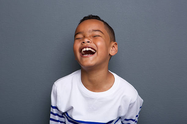 Excited little boy laughing Close up portrait of an excited little boy laughing on gray background 8 9 years stock pictures, royalty-free photos & images