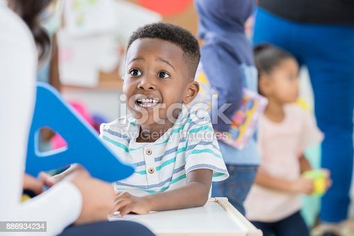 istock Excited little boy recognizes letter A at preschool 886934234
