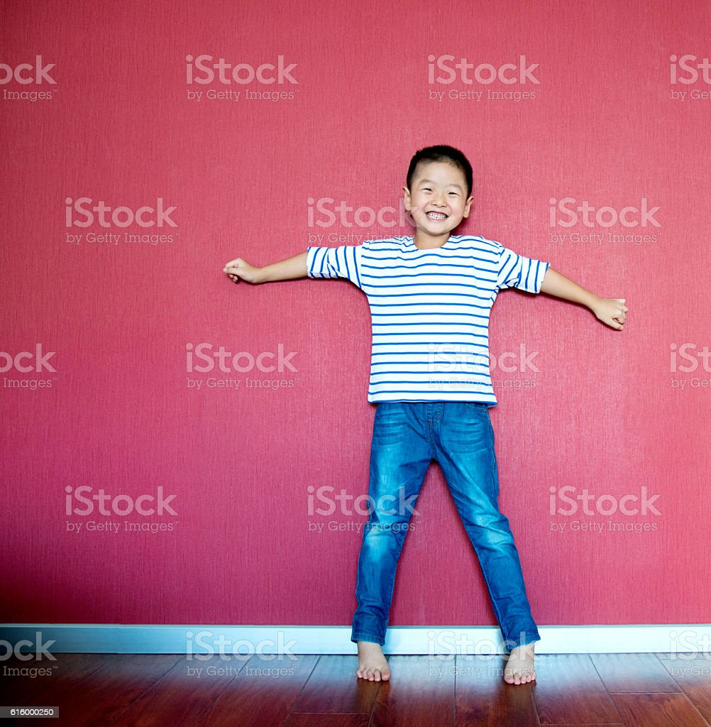 Excited little boy standing against wall stock photo