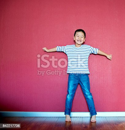 istock Excited little boy standing against wall 842217706