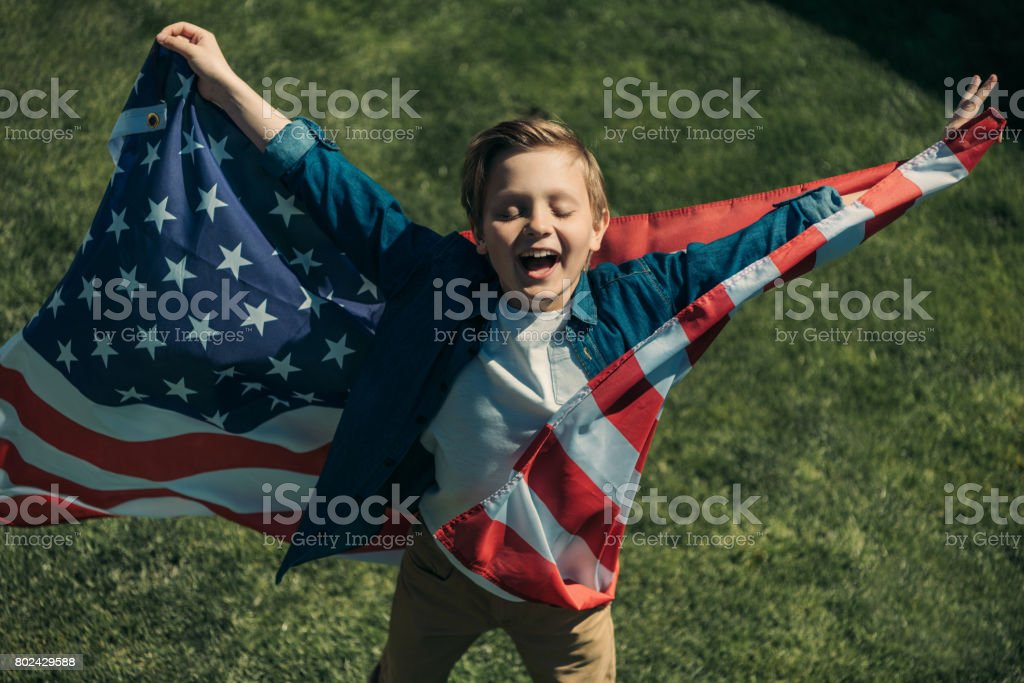 excited little boy with american flag, America's Independence Day concept stock photo