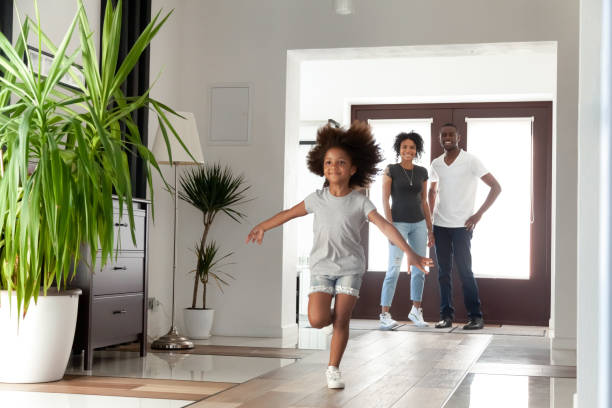 Excited little funny african girl running exploring big modern house on moving day Excited little funny african girl running exploring big modern house moving in, happy black parents and kid daughter coming into new home, cute mixed race child having fun in hallway, family mortgage entering stock pictures, royalty-free photos & images