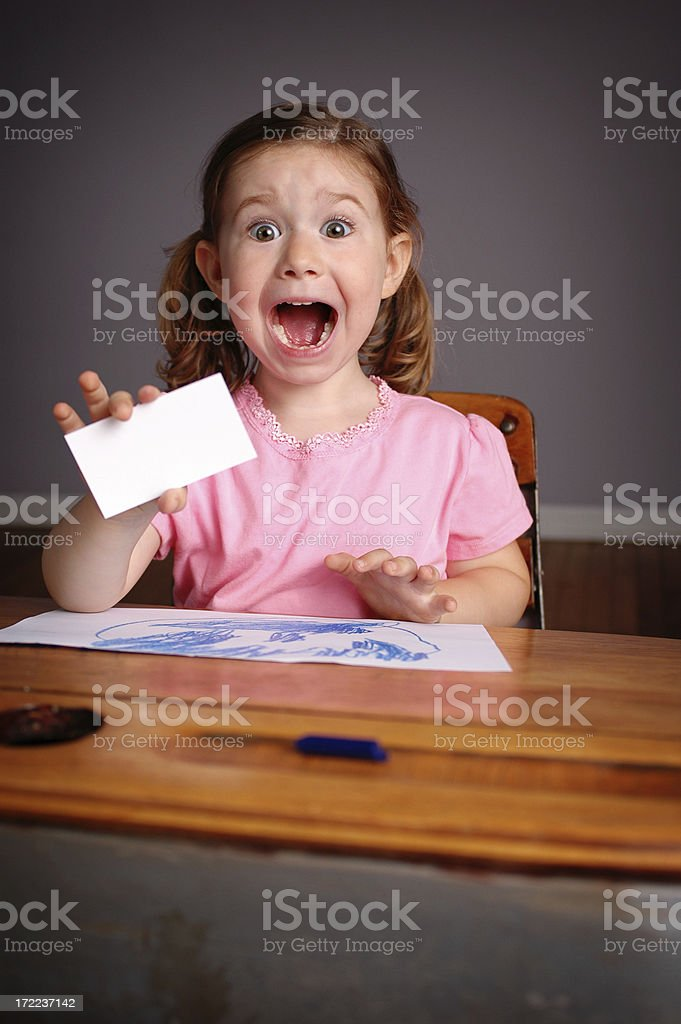 Excited Little Girl in School Desk Holding Business Card royalty-free stock photo