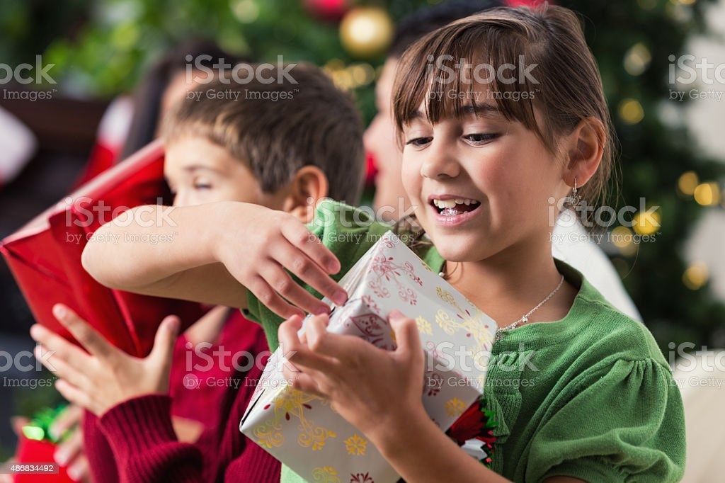 Excited little girl unwrapping Christmas presents with family stock photo