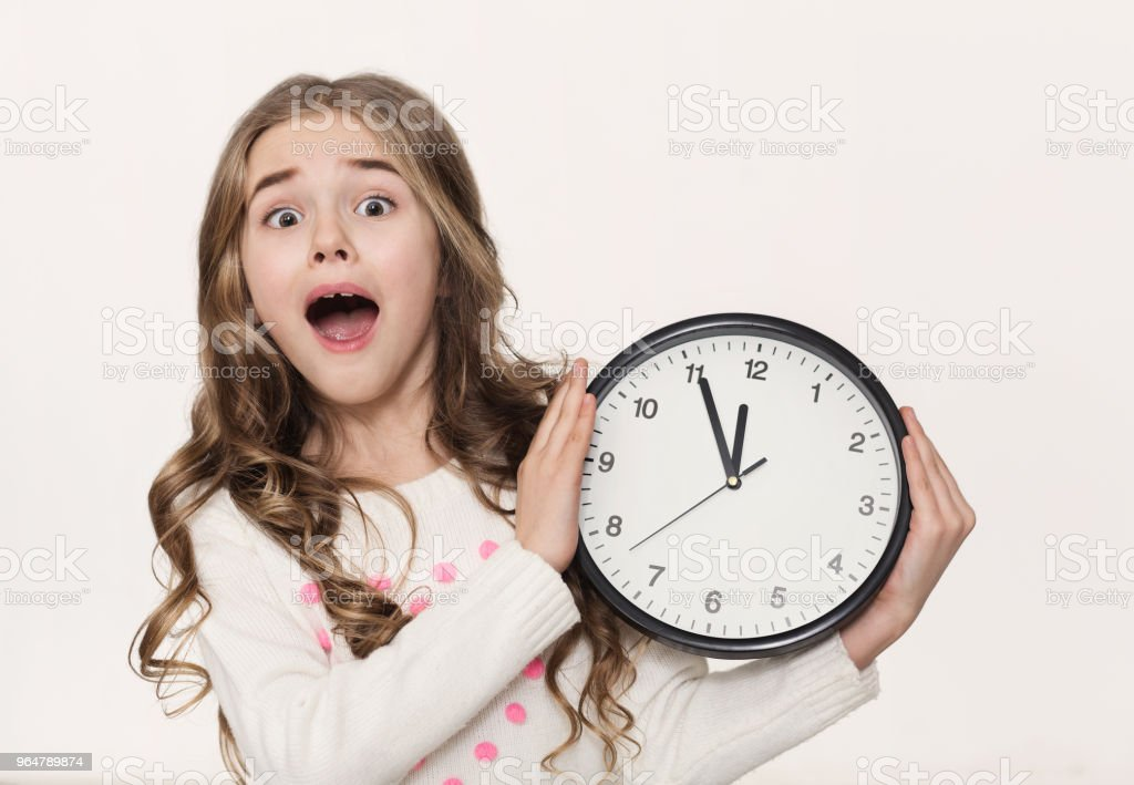 Excited little girl with clock at white background royalty-free stock photo