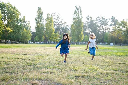 Excited little girls running on grass