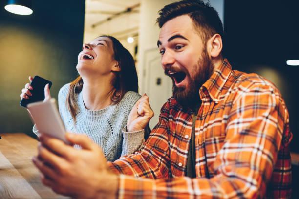 os hipsters masculinos e fêmeas excited regozijam-se em ganhar uma loteria do internet fizeram apostas no web site no smartphone moderno. pares felizes no amor que comemora a vitória em competições em linha que apreciam o sucesso - em êxtase - fotografias e filmes do acervo