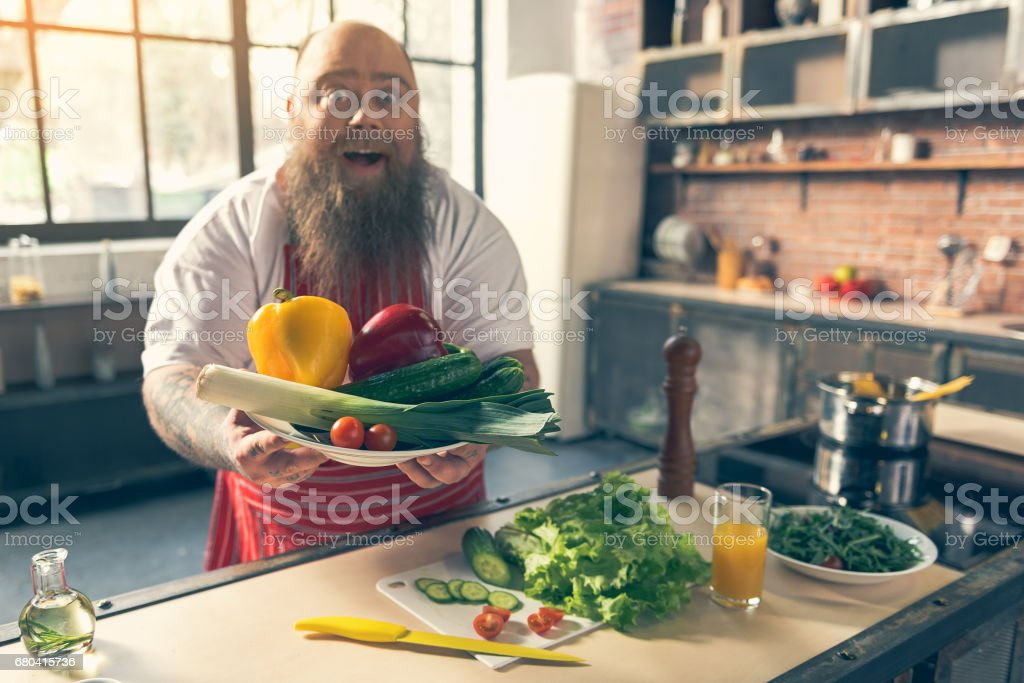 Excited male fatso showing healthy food stock photo
