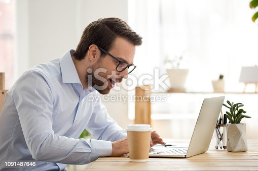 istock Excited male look at laptop screen reading great news online 1091487646