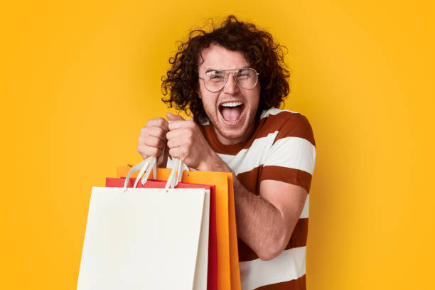 opgewonden man met boodschappentassen - shopaholic stockfoto's en -beelden