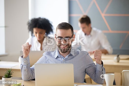 istock Excited male worker winning online lottery sitting in coworking space 994164910