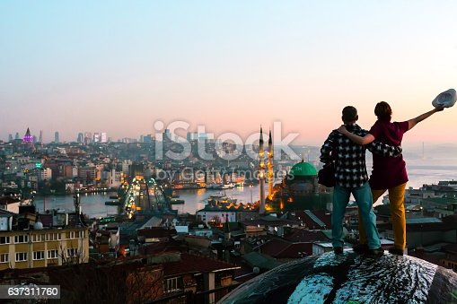 Excited Man and Woman staying on top of building and overlooking Asian city at sunrise
