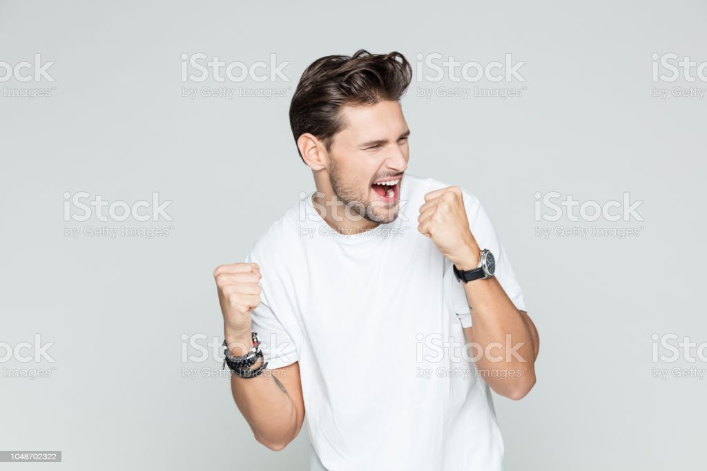 Excited man celebrating success Portrait of young excited man celebrating success, looking away and cheering on grey background 25-29 Years Stock Photo