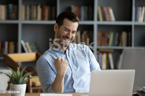 Excited man wearing glasses celebrating success, reading good news in email, happy overjoyed businessman looking at laptop screen, showing yes gesture and laughing, sitting at work desk