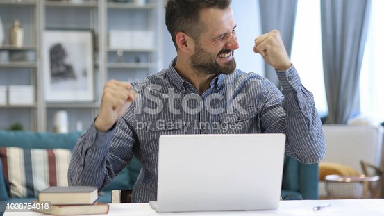 888751614 istock photo Excited Man Celebrating Success, Working on Laptop 1038754018