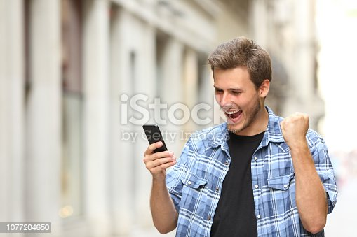 istock Excited man checking news on phone in the street 1077204650