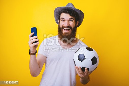843298172 istock photo Excited man holding a soccer ball and his smartphone. Watching soccer match, online mobile streaming. Sport betting. 1193906577