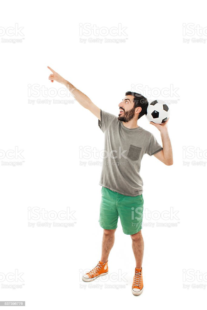 Excited man holding football, pointing stock photo