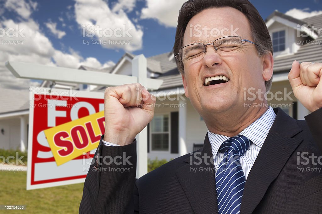 Excited Man in Front of Sold Sign and New House royalty-free stock photo