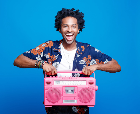 istock Excited man in hawaiian shirt holding pink boom box 1214690201