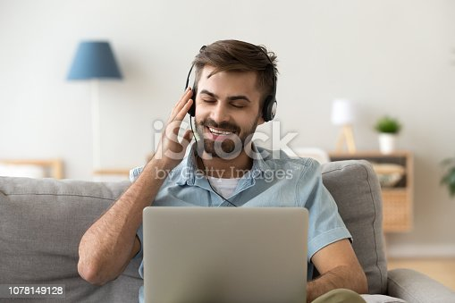 Happy millennial man wearing headset sit on sofa listening to music on laptop, excited male in earphones enjoy favorite track playing on computer online, smiling guy have fun at home
