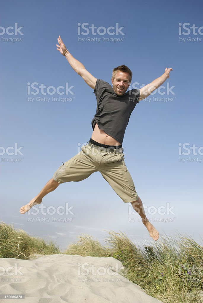 Excited Man in T-Shirt Jumping Over Sand Dune stock photo