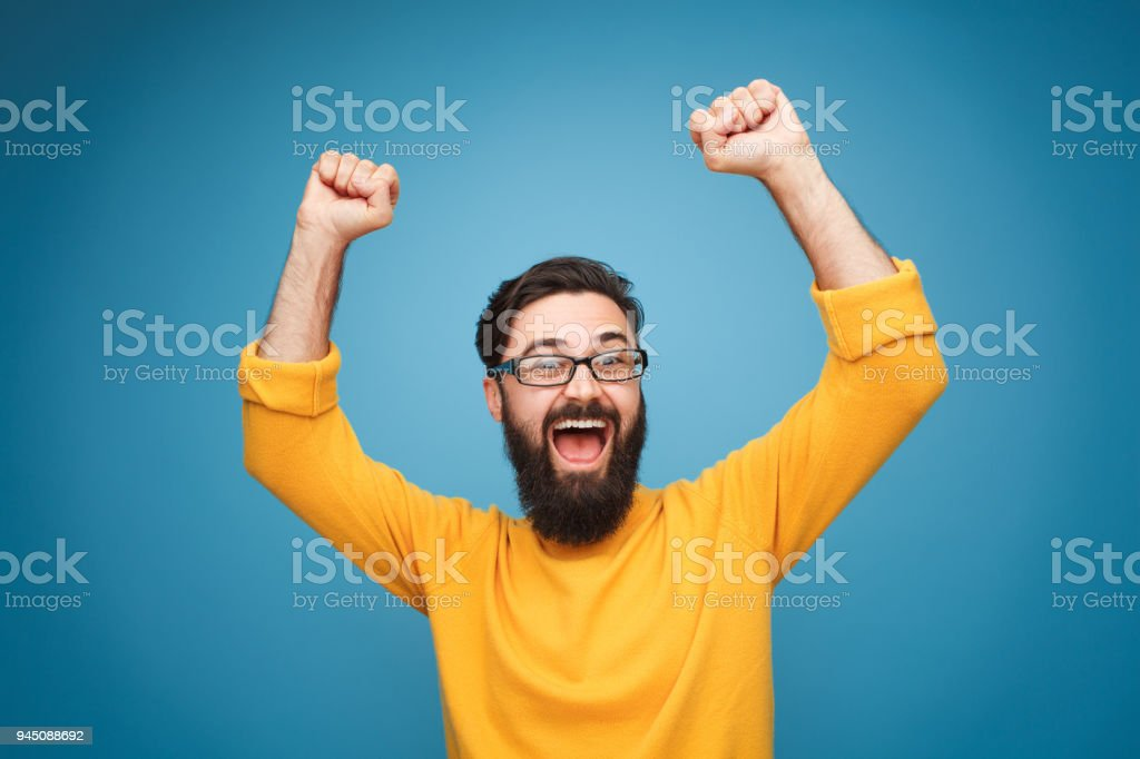 Excited man in yellow holding hands up royalty-free stock photo