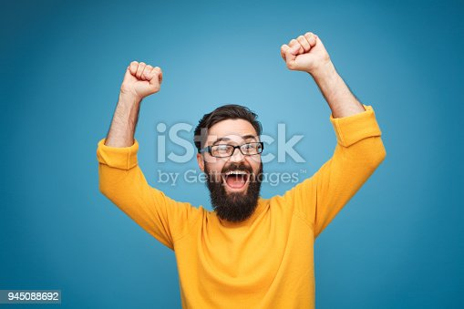 istock Excited man in yellow holding hands up 945088692