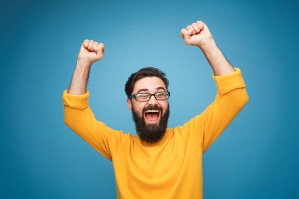 Excited man in yellow holding hands up stock photo
