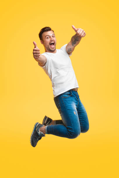 Excited man jumping and gesturing thumb up Handsome young guy in casual outfit screaming and showing thumb up gesture with both hands while looking at camera and jumping on bright yellow background mid air stock pictures, royalty-free photos & images