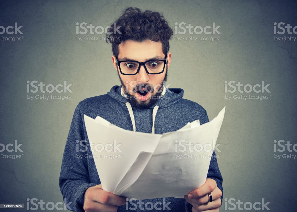 Excited man looking at papers in shock stock photo